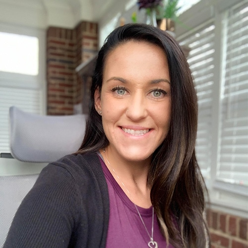 Portrait of a White Lady Smiling at the Camera wearing a purple t-shirt and a black cardigan. Michelle