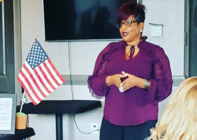 Chanda Giving a Speech in a classroom with an American Flag on the table
