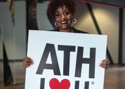 """Portrait of an African-American Lady holding up a sign saying """"ATH I love you"""""""