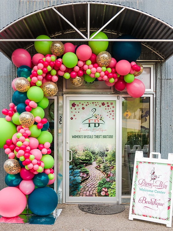 Photo of Building Representing Freedom Boutique with Colorful Balloons and poster with Divas Who Win Branding