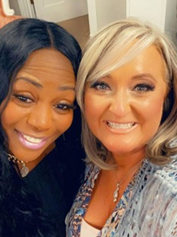 Selfie of Smiling African-American Lady and White Lady looking into the camera